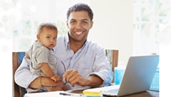 Father with baby and laptop.